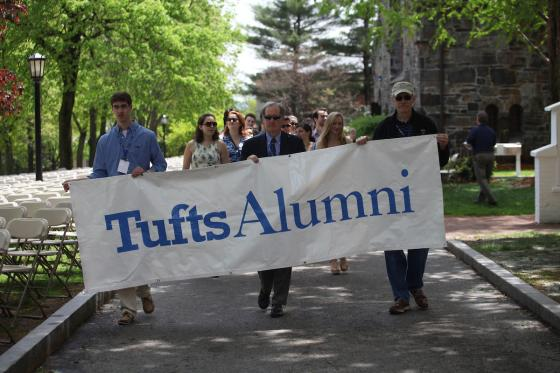 "People walking with a banner that says ""Tufts Alumni"""