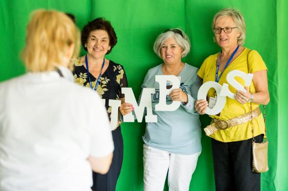 "Women standing in front of a green screen holding letters that spell ""Jumbos"""