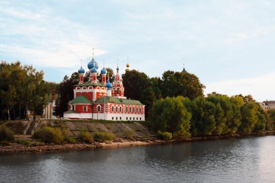 A Russian Orthodox church is seen on the banks of a river sitting among trees