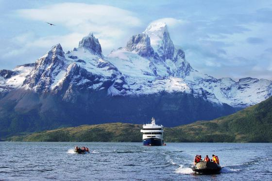 A cruise ship and two smaller boats in the sea with a large snow topped mountain in the background