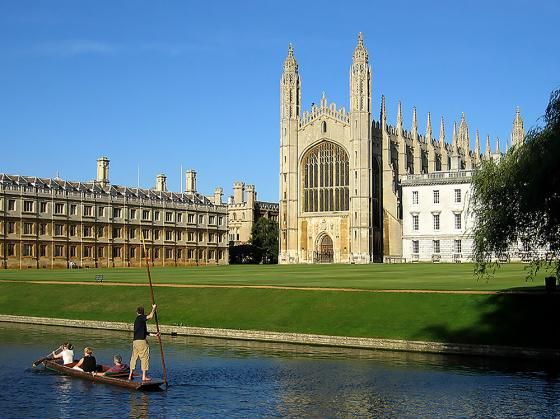 View of Oxford University in England, gothic stone buildings on a grassy lawn with a waterway, in the waterway there is a boat of people and one person standing rowing