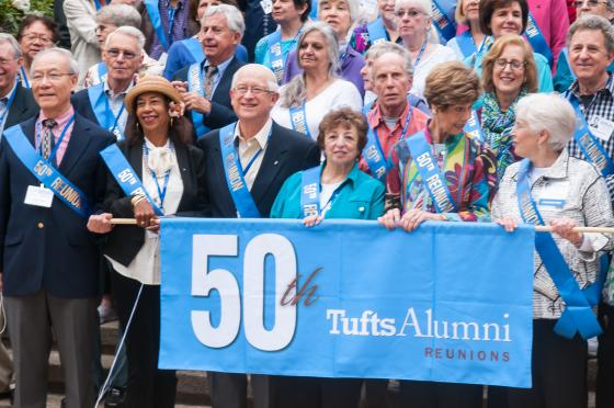 A group of people holding up a 50th reunion banner