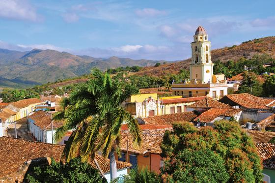 View of a South American colonial village in the mountains, a church tower is easily seen coming up from the red roofs