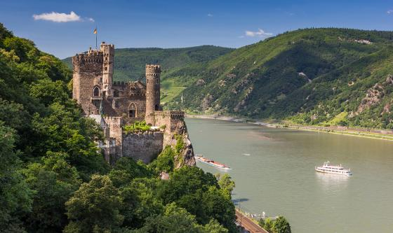 A stone castle stands between two mountains on the banks of a river