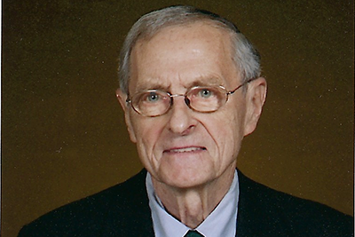 Portraite of an older white male, gray hair and glasses, wearing a suit.