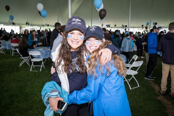Two young women wearing Tufts hats and blue jackets embrace during Homecoming at the university in 2017.
