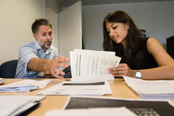 Older man reviewing documents with younger woman