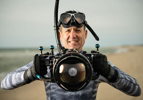 Tom Burns, on Cape Cod's Nauset Beach, wearing underwater gear and standing on a beach with one of his cameras.