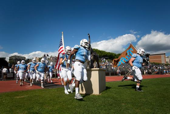 Tufts' football team runs onto the field for the Homecoming 2018 game on the Medford/Somerville campus.