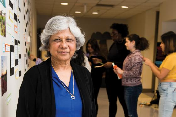Professor Jayanthi Mistry stands in a hallway with students in the background.