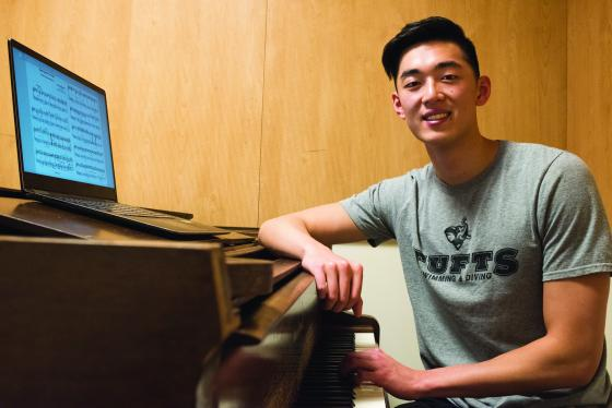 Roger Gu sits by a piano