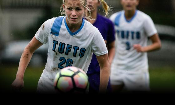 Tufts women's soccer team members chase a soccer ball