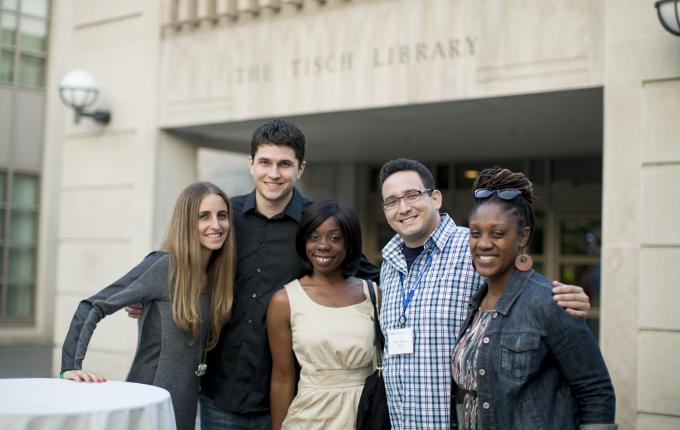 Tufts alumni pose for a photo in front of the Tisch Library