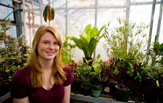 Student sitting in a greenhouse surrounded by plants