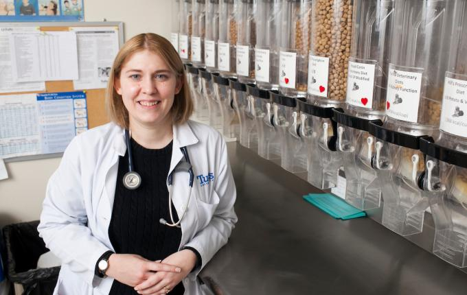 Vet student stand in front of many dispensers with pet food lined up