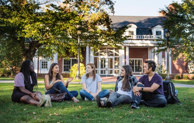 Group of students sits talking on a lawn in front of a colonial brick mansion
