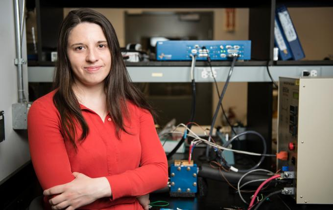 Stuent poses in front of her research, a workbench with various electronic instruments