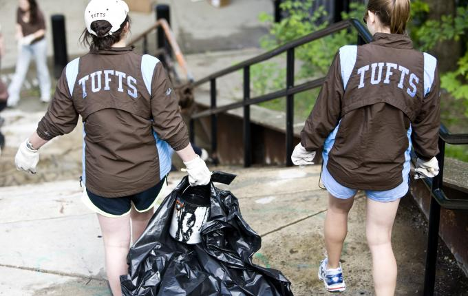 Two women walking down steps carrying trash bags