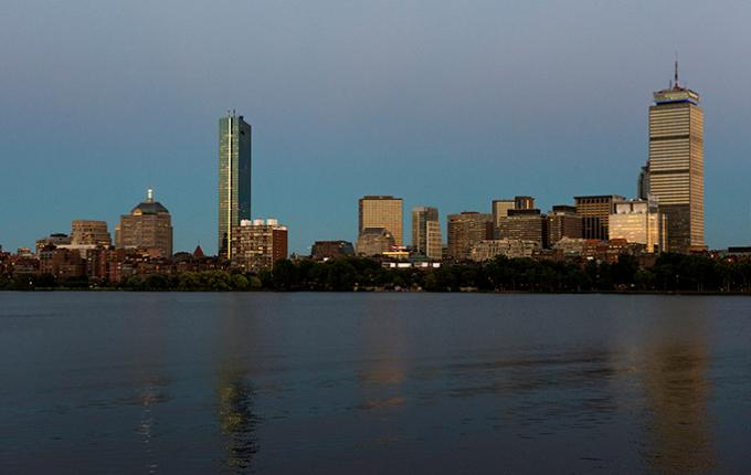 A view of the Boston skyline in the evening taken from across the river in Cambridge.